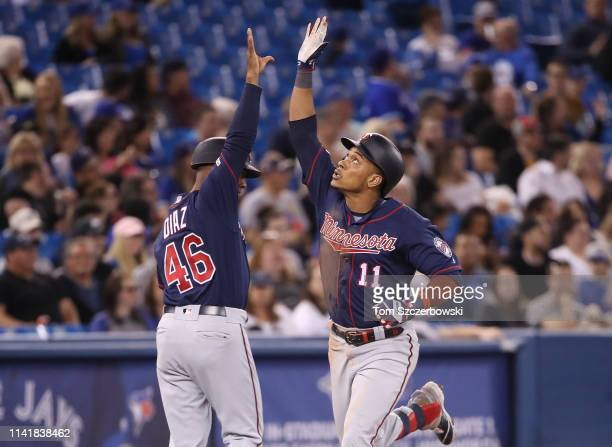 Jorge Polanco of the Minnesota Twins is congratulated by third base coach Tony Diaz after hitting a solo home run in the seventh inning during MLB...