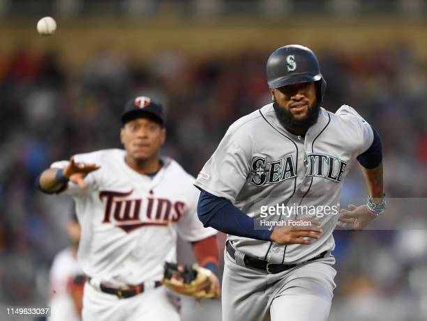 Jorge Polanco of the Minnesota Twins passes the ball over Domingo Santana of the Seattle Mariners after Santana was caught off first base during the...