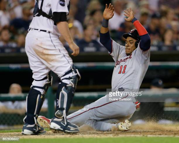 Jorge Polanco of the Minnesota Twins slides in safe at home plate to score against the Detroit Tigers on a single by Eduardo Escobar of the Minnesota...
