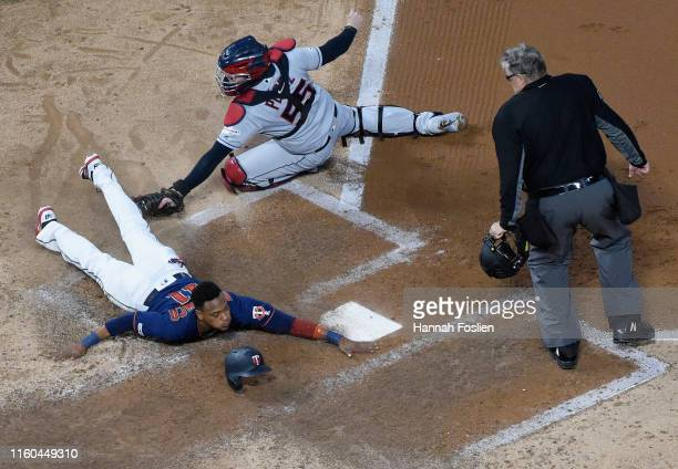 Jorge Polanco of the Minnesota Twins slides safely past Roberto Perez of the Cleveland Indians to score as umpire Gary Cederstrom looks on during the...