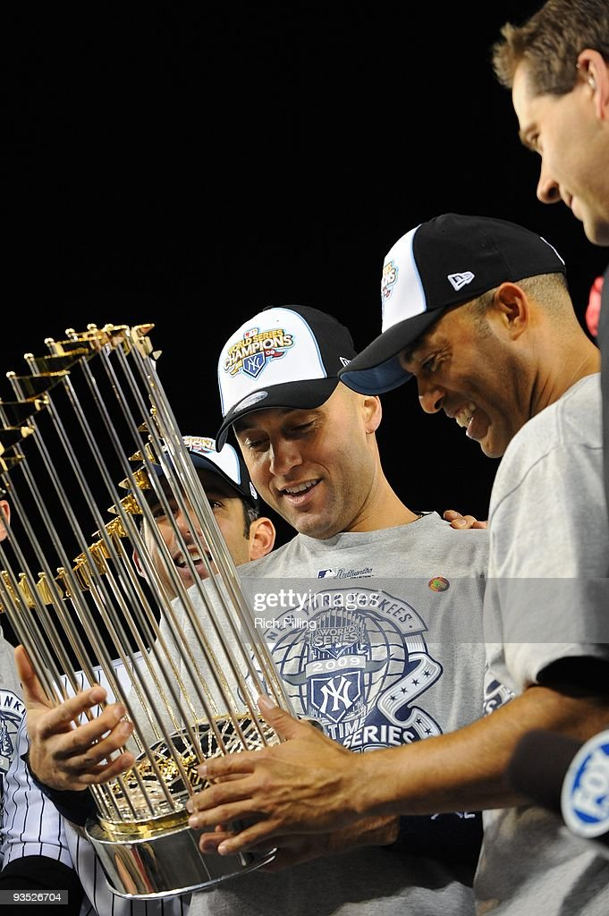 Jorge Posaada #20, Derek Jeter #2 and Mariano Rivera #42 of the New York Yankees hold the World Series trophy after their 7-3 win over the Philadelphia Phillies in Game Six of the 2009 MLB World Series at Yankee Stadium on November 4, 2009 in New York, New York.