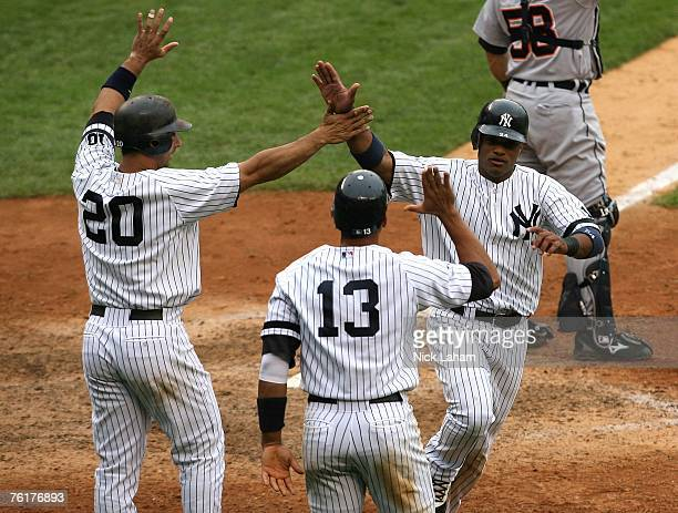 Jorge Posada Alex Rodriguez and Robinson Cano of the New York Yankees celebrate scoring after a Wilson Betemit double in the bottom of the eighth...