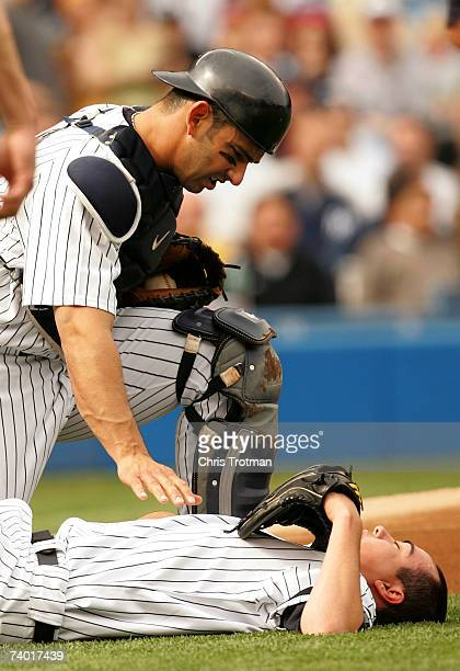 Jorge Posada checks on his teammate Jeff Karstens the starting pitcher of the New York Yankees after he is hit on the knee by a line drive on his...