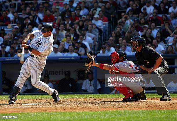 Jorge Posada of the New York Yankees bats as catcher Doug Mirabelli of the Boston Red Sox and home plate umpire Mike DiMuro watch during the game at...
