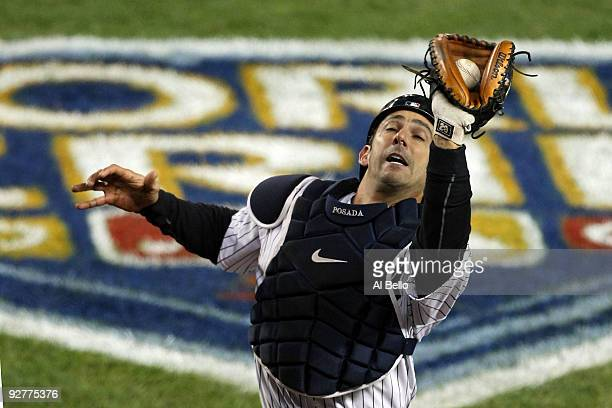 Jorge Posada of the New York Yankees catches a pop fly for the third out in the top of the eighth inning against Pedro Feliz of the Philadelphia...