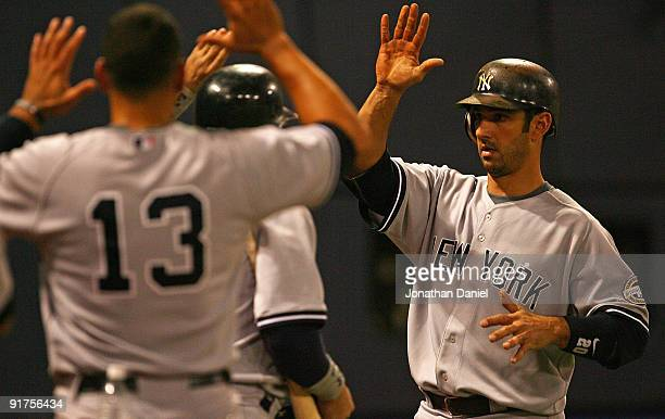 Jorge Posada of the New York Yankees is greeted by teammates including Alex Rodriguez, after hitting a solo home run in the 7th inning against the...