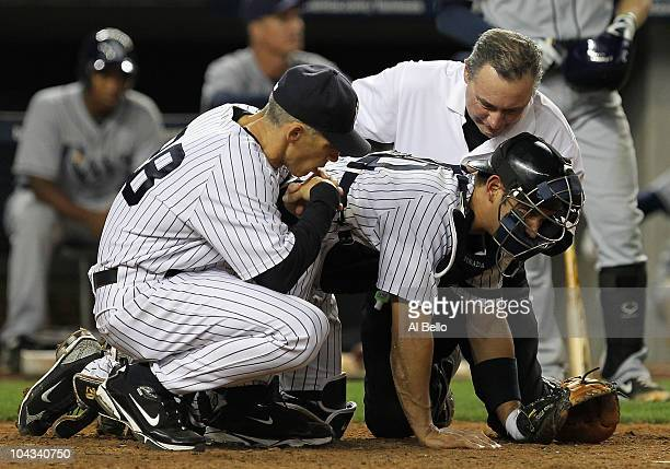 Jorge Posada of the New York Yankees is met by Manager Joe Girardi and a trainser after being hit with a foul tip in the ninth inning against the...