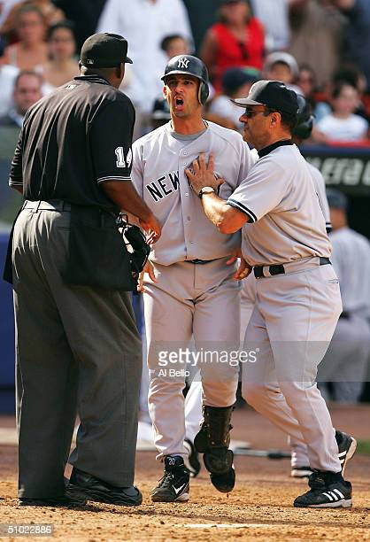 Jorge Posada of the New York Yankees is restrained by manager Joe Torre after Posada was called out on strikes with bases loaded by home plate umpire...
