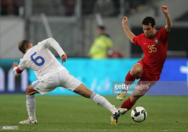 Jorge Ribeiro of Portugal passes over Angelos Basinas of Greece during the international friendly match between Portugal and Greece at the LTU Arena...