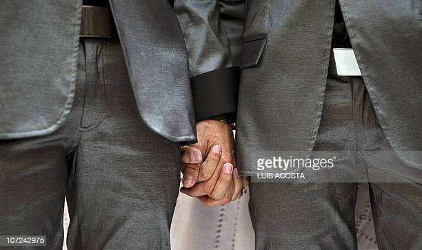 Jorge Saavedra and Gabriel Rodriguez hold hands during their marriage on the World AIDS Day in Mexico City on December 1 2010 AFP PHOTO/Luis Acosta