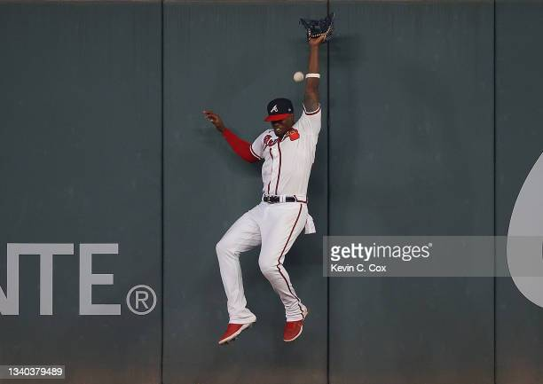 Jorge Soler of the Atlanta Braves lands on the outfield wall as he fails to catch this fly ball hit by Garrett Hampson of the Colorado Rockies in the...