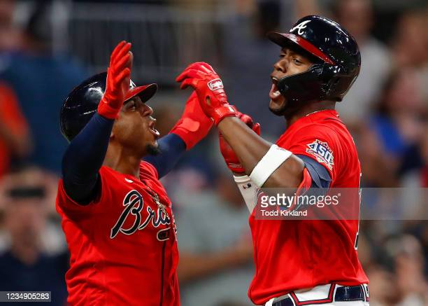 Jorge Soler of the Atlanta Braves reacts with Ozzie Albies after hitting a three-run home run in the seventh inning of an MLB game against the San...