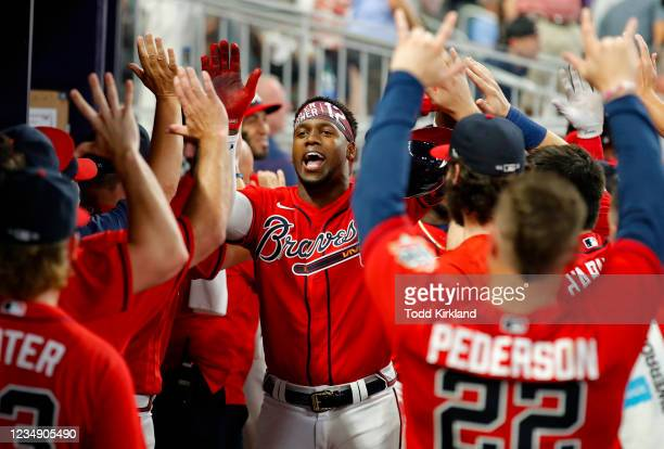 Jorge Soler of the Atlanta Braves reacts with teammates after hitting a three-run home run in the seventh inning of an MLB game against the San...
