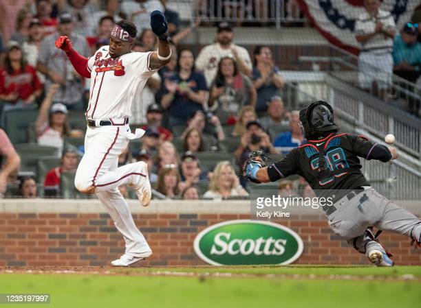 Jorge Soler of the Braves avoids the tag by Marlins catcher Jorge Alfaro to score a run in the 5th inning at Truist Park on September 11, 2021 in...