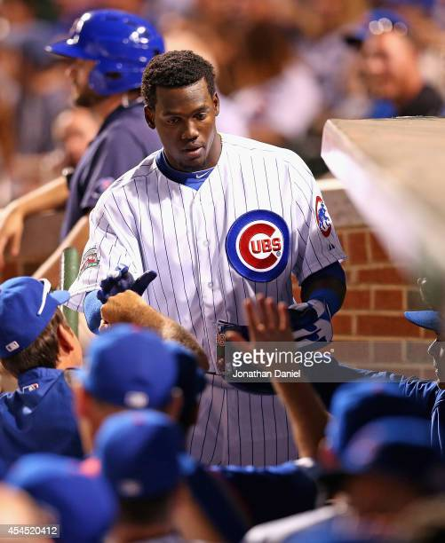 Jorge Soler of the Chicago Cubs is congratulated by coaches and teammates after scoring a run in the 1st inning against the Milwaukee Brewers at...