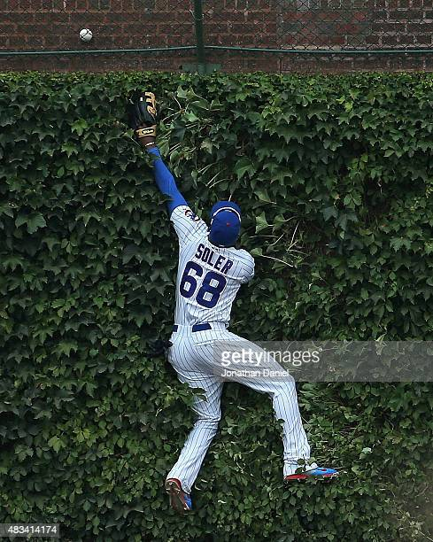 Jorge Soler of the Chicago Cubs jumps up against the outfield wall trying to catch a home run ball hit by Brandon Belt of the San Francisco Giants in...