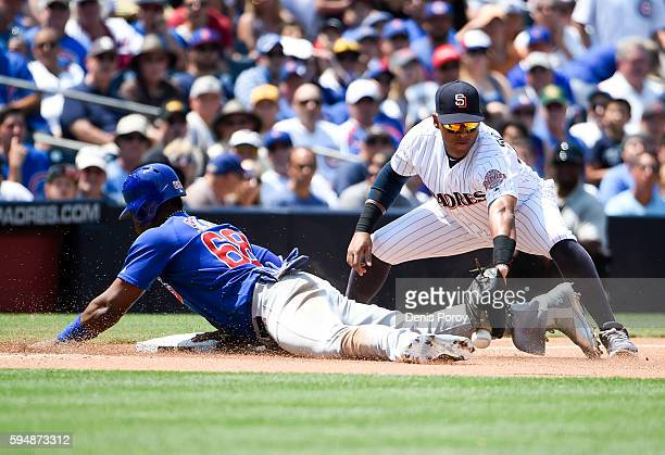 Jorge Soler of the Chicago Cubs slides into third base as Yangervis Solarte of the San Diego Padres loses the ball during the fourth inning of a...