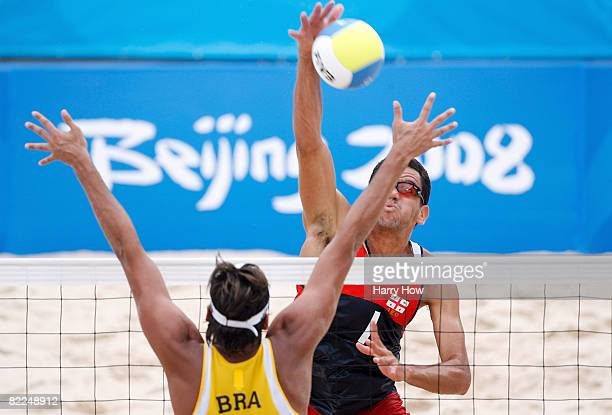 Jorge Terceiro of Georgia spikes the ball against Ricardo Santos of Brazil during the beach volleyball event at the Chaoyang Park Beach Volleyball...