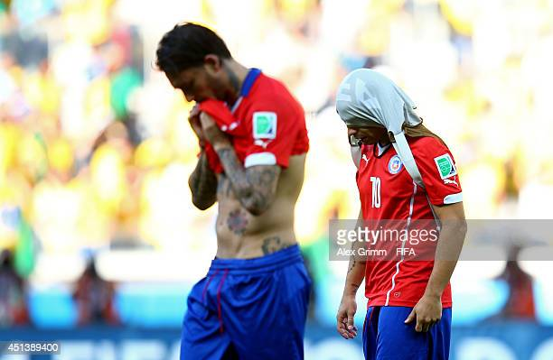 Jorge Valdivia and Mauricio Pinilla of Chile walk off the pitch after the 2014 FIFA World Cup Brazil Round of 16 match between Brazil and Chile at...