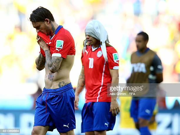Jorge Valdivia and Mauricio Pinilla of Chile walk off the pitch after the defeat in the 2014 FIFA World Cup Brazil Round of 16 match between Brazil...