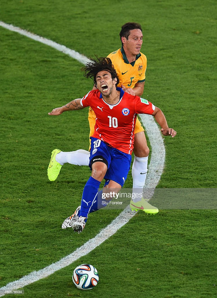 Jorge Valdivia of Chile falls after a challenge by Mark Milligan of Australia during the 2014 FIFA World Cup Brazil Group B match between Chile and Australia at Arena Pantanal on June 13, 2014 in Cuiaba, Brazil.