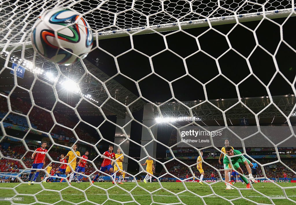 Jorge Valdivia of Chile (obscured) shoots and scores his team's second goal against goalkeeper Mathew Ryan of Australia during the 2014 FIFA World Cup Brazil Group B match between Chile and Australia at Arena Pantanal on June 13, 2014 in Cuiaba, Brazil.