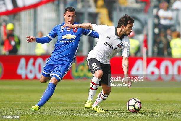 Jorge Valdivia of ColoColo struggles for the ball with Sebastian Ubilla of U de Chile during a match between ColoColo and Universidad de Chile as...