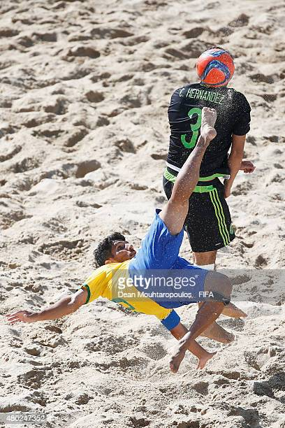 Jorginho of Brazil attempts a scissor kick shot on goal in front of Carlos Hernandez of Mexico during the Group C FIFA Beach Soccer World Cup match...