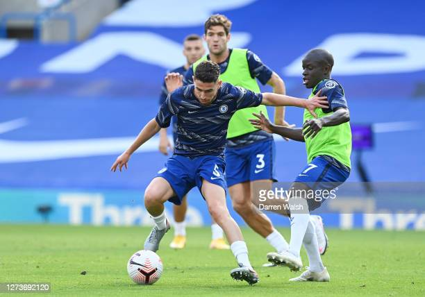 Jorginho of Chelsea is challenged by N'Golo Kante of Chelsea during the warm up prior to the Premier League match between Chelsea and Liverpool at...