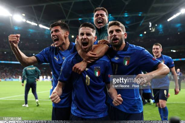 Jorginho of Italy celebrates with Matteo Pessina and Domenico Berardi after scoring their sides winning penalty in the penalty shoot out during the...