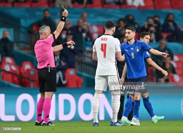 Jorginho of Italy clashes with Declan Rice of England as Match Referee, Bjoern Kuipers shows Nicolo Barella of Italy a yellow card during the UEFA...