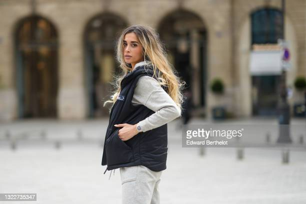 Jori Delli wears a pale gray hoodie sport sweater from Asos, matching pale gray sport pants from Asos, a black sleeveless Prada puffer gilet, a...