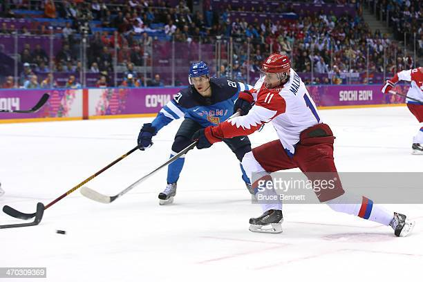 Jori Lehtera of Finland and Yevgeni Malkin of Russia chase the puck during the Men's Ice Hockey Quarterfinal Playoff on Day 12 of the 2014 Sochi...