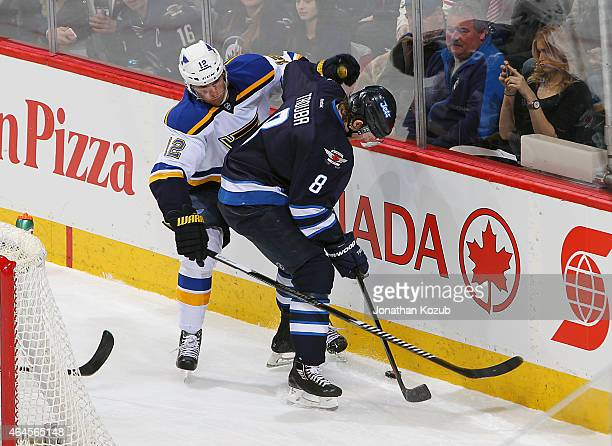Jori Lehtera of the St. Louis Blues and Jacob Trouba of the Winnipeg Jets battle for the puck along the boards during second period action on...