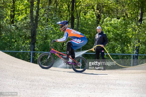 Joris Harmsen in action while head coach Raymon van der Biezen is spraying the track with water at the Dutch top BMX riders first training at...
