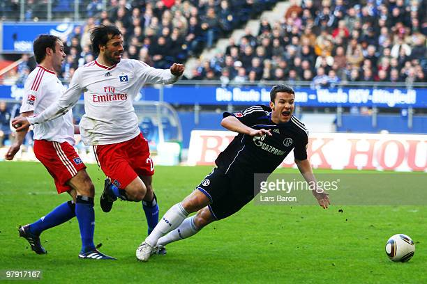 Joris Mathijsen and Ruud van Nistelrooy of Hamburg challenge Alexander Baumjohann of Schalke in the penalty box during the Bundesliga match between...