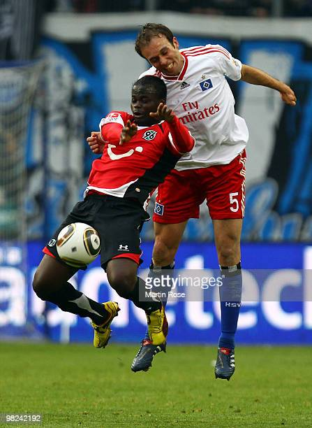 Joris Mathijsen of Hamburg and Didier Ya Konan of Hannover compete for the ball during the Bundesliga match between Hamburger SV and Hannover 96 at...