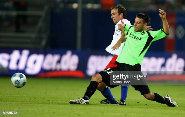 Joris Mathijsen of Hamburg and Mikkel Beckmann of Randers compete for the ball during the UEFA Europa League second leg match between Hamburger SV...