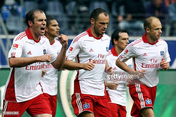 Joris Mathijsen of Hamburg celebrates his team's first goal with team mates Heiko Westermann and David Jarolim during the Bundesliga match between...