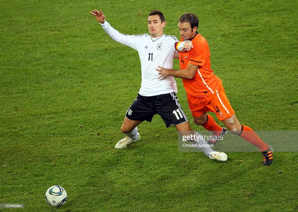 Joris Mathijsen of Netherlands (R) challenges Miroslav Klose (L9 of Germany during the International Friendly match between Germany and Netherlands at Imtech Arena on November 15, 2011 in Hamburg, Germany.
