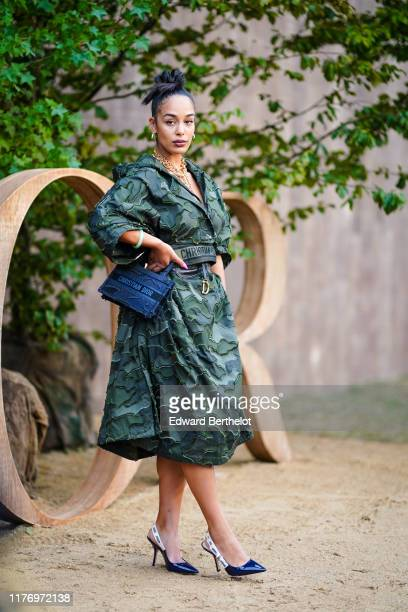 Jorja Smith wears a green military camouflage printed dress with embroidery, a Dior bag, a Dior belt, Dior pointy shoes, earrings, a golden necklace,...