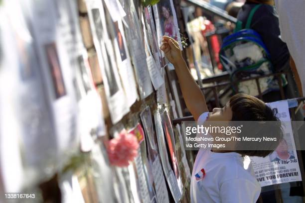 Jorman Vasquez puts a flower on one of the missing persons flyers at 26th Street and Lexington Avenue, across from the Armory, in New York City on...