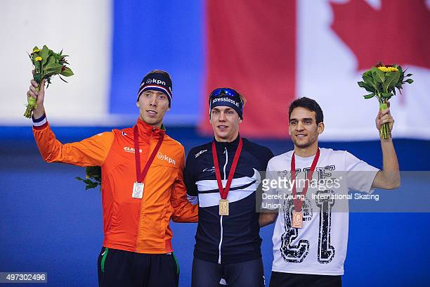 Jorrit Bergsma of The Netherlands Bart Swings of Belarus and Reyon Kay of New Zealand stand on the podium after the Men's Mass Start during the ISU...