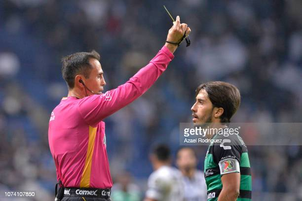 José Abella of Santos argues with referee Luis Enrique Santander who gave a yellow card to Martin Nervo of Santos during the quarter finals first leg...