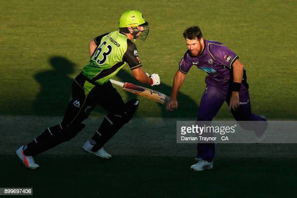 Jos Butler of the Sydney Thunder takes a run as Dan Christian of the Hobart Hurricanes chases the ball during the Big Bash League match between the...
