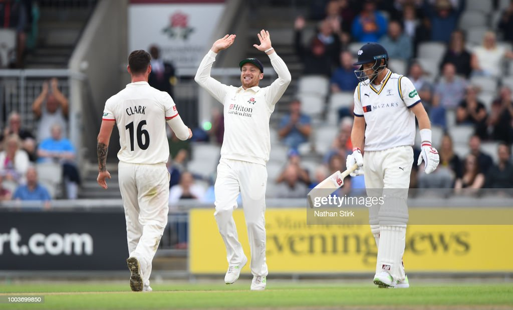 Jos Buttler high fives Jordan Clark of Lancashire after he gets Joe Root of Yorkshire out during the Specsavers Championship Division One match between Lancashire and Yorkshire at Old Trafford on July 22, 2018 in Manchester, England.