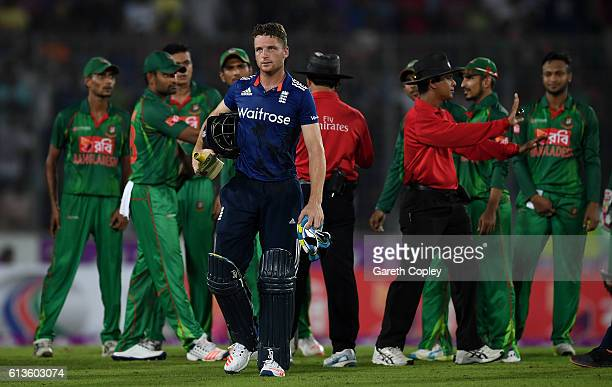 Jos Buttler leaves the field as umpires Aleem Dar and Sharfuddoula separate his from the Bangladesh fielders during the 2nd One Day International...