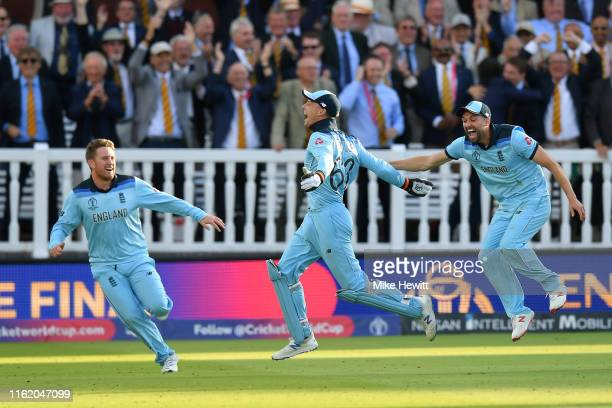 Jos Buttler Mark Wood and Liam Dawson of England celebrate in front of the Lord's members after victory off the last ball of the super over at the...