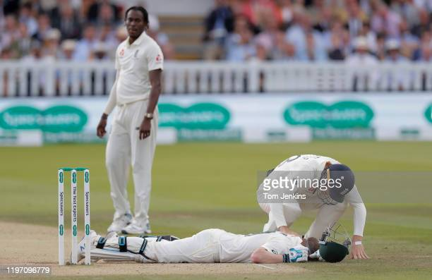 Jos Buttler of England aids Steve Smith of Australia after he collapsed to the ground after being hit on the back of the head by a ball from Jofra...