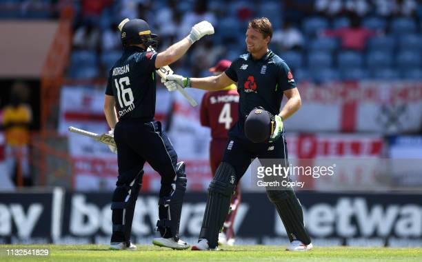 Jos Buttler of England celebrates reaching his century with captain Eoin Morgan during the 4th One Day International match between the West Indies...